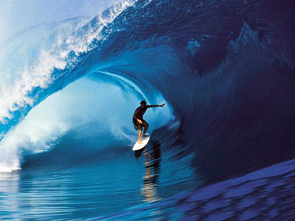 a surfer surfing on blue water
